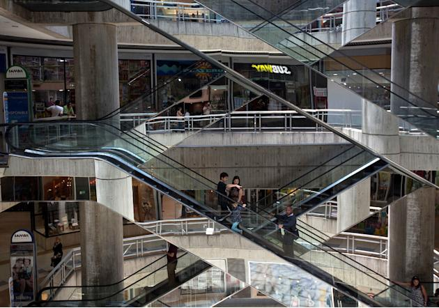 In this April 10, 2014 photo, people ride the nearly empty escalators inside Sambil mall in the city in Caracas, Venezuela. Fifteen years of socialist rule and an acute economic crisis is catching up