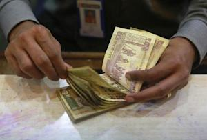 A cashier counts Indian rupee currency notes inside a bank in Mumbai