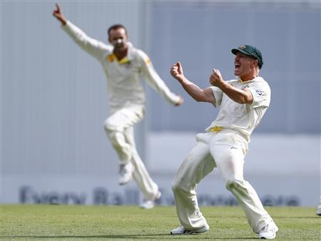Australia's David Warner (R) and bowler Nathan Lyon celebrate after Warner took the catch to dismiss England's Matt Prior during the fourth day's play of the first Ashes cricket test match in Brisbane November 24, 2013. REUTERS/David Gray