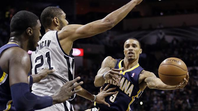Indiana Pacers' George Hill (3) passes around San Antonio Spurs' Tim Duncan (21) to teammate Roy Hibbert, left, during the first half on an NBA basketball game Saturday, Dec. 7, 2013, in San Antonio