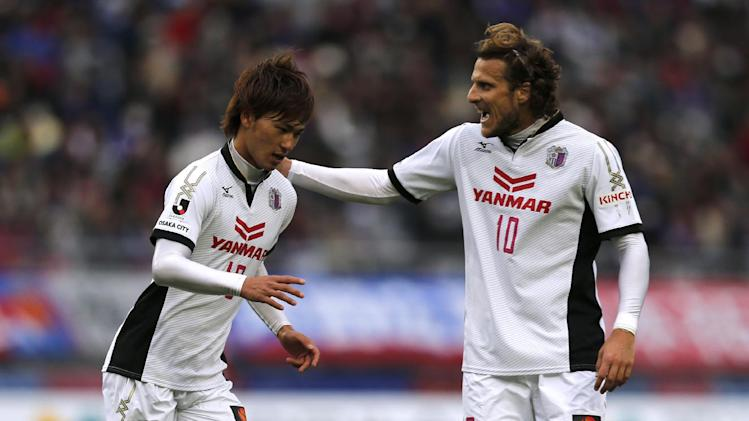 Cerezo Osaka's Diego Forlan of Uruguay, right, pats on the shoulder of teammate Takumi Minamino after Minamino's attempt to score a goal against FC Tokyo during a J-League soccer  match in  Tokyo, Saturday, April 19, 2014