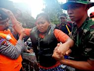 Indonesian military evacuate a woman from a flooded area in Jakarta, on January 18, 2013. The death toll from floods in Indonesia's capital has risen to 15 after rescuers found another four bodies, a police spokesman said on Saturday as floodwaters receded