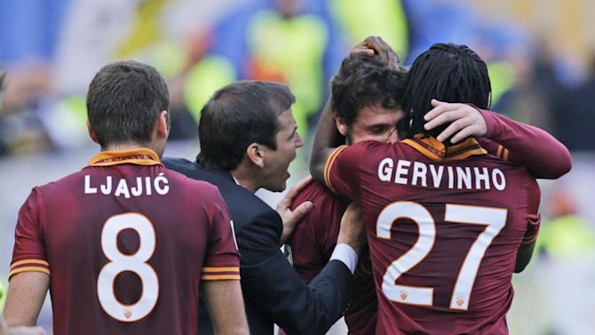 AS Roma forward Mattia Destro, second from right, celebrates with his teammates, from left, Adem Ljajic, of Serbia, coach Rudi Garcia, of Franc,e and Gervinho, of the Ivory Coast, after he scored during a Serie A soccer match between AS Roma and Fiorentina, at Rome's Olympic Stadium, Sunday, Dec. 8, 2013. AS Roma won 2-1