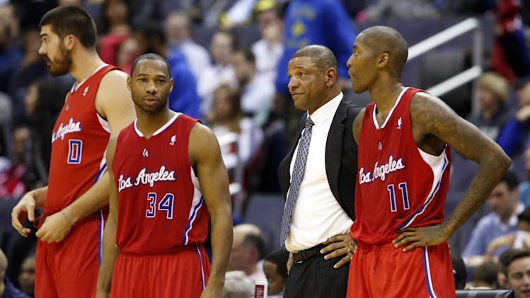 Los Angeles Clippers head coach Doc Rivers smiles as he stands between center Byron Mullens (0), guard Willie Green (34) and guard Jamal Crawford (11) in the second half of an NBA basketball game, Saturday, Dec. 14, 2013, in Washington. The Clippers won 113-97
