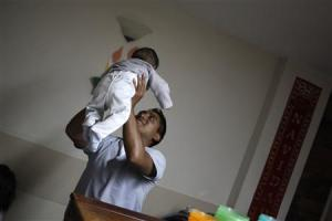 A nurse carries a child in the San Jose Hospice in Sacatepequez