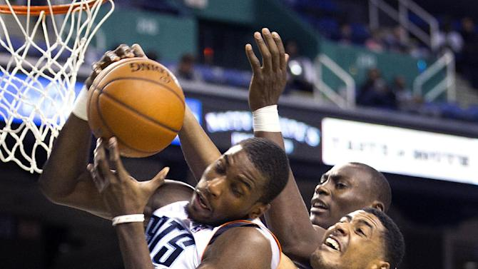 Charlotte Bobcats' Michael Kidd-Gilchrist fights for the rebound with Dallas Mavericks' Fab Melo (14) with Bobcat's Charlotte Bobcats' Bismack Biyombo (0) during the second half of a preseason NBA basketball game at the Greensboro Coliseum in Greensboro, N.C., Saturday, Oct. 19, 2013
