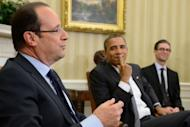 US President Barack Obama (R) listens as French President Francois Hollande speaks following their bilateral meeting in the Oval Office at the White House