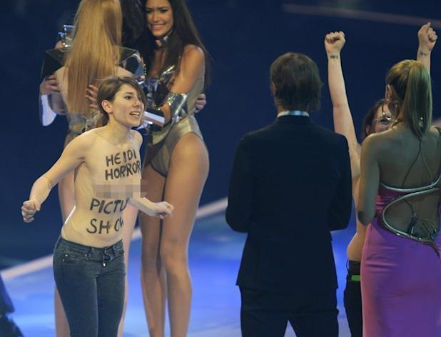 """Two activists of the Femen feminist group protest on stage during the final of Heidi Klum's (R) """"Germany's Next Topmodel"""" TV show in Mannheim, southern Germany on May 30, 2013. Two bare-breasted female protesters burst on to the stage during the final hoted by Klum late Thursday"""