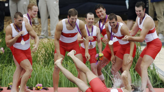 Members of Canada's men's rowing eight throw a teammate in Lake Dorney after winning the silver medal in Eton Dorney, near Windsor, England