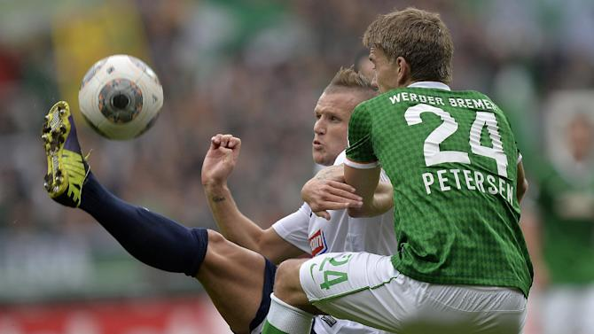 Freiburg's Jonathan Schmid of France, left, and Bremen's Nils Petersen challenge for the ball during the German first division Bundesliga soccer match between Werder Bremen and SC Freiburg in Bremen, Germany, Saturday, Oct. 19, 2013