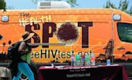 A woman walks past a truck offering free HIV testing on the spot at a Women's Day in the Park event in Los Angeles in May. A cure for AIDS remains a distant prospect but a host of drug treatments and other advances have fueled fresh hope that new human immunodeficiency virus infections may some day be halted for good