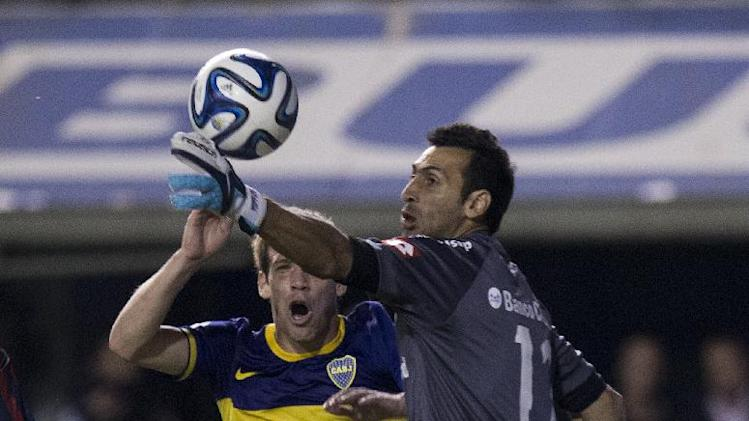San Lorenzo's goalkeeper Sebastian Torrico blocks the ball from Boca Juniors' Claudio Riano in the last minute of an Argentine league soccer match in Buenos Aires, Argentina, Wednesday, April 16, 2014. The match ended 0-0