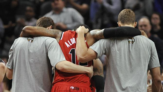 Portland Trail Blazers forward LaMarcus Aldridge, center, is helped from the court after suffering an injury during the second half of an NBA basketball game against the San Antonio Spurs on Wednesday, March 12, 2014, in San Antonio. San Antonio won 103-90