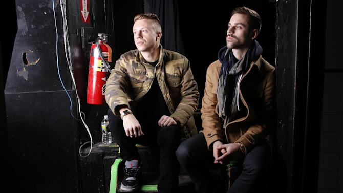"""FILE - This Nov. 20, 2012 file photo shows Ben Haggerty, better known by his stage name Macklemore, left, and his producer Ryan Lewis at Irving Plaza in New York. The rapper Macklemore thinks there's a simple reason his hit """"Thrift Shop"""" appears to be going viral: It dares to be different. The Seattle-based duo has sold 2.3 million copies so far _ a million in the last month alone _ and sales continue to grow week to week. (Photo by Carlo Allegri/Invision/AP, file)"""