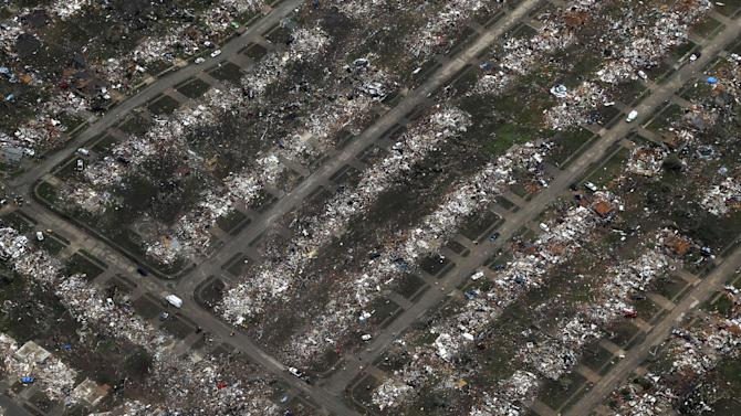 This aerial view shows an entire neighborhood destroyed by Monday's tornado, Tuesday, May 21, 2013, in Moore, Okla. A huge tornado roared through the Oklahoma City suburb Monday, flattening  entire neighborhoods and destroying an elementary school with a direct blow as children and teachers huddled against winds. (AP Photo/Tony Gutierrez)