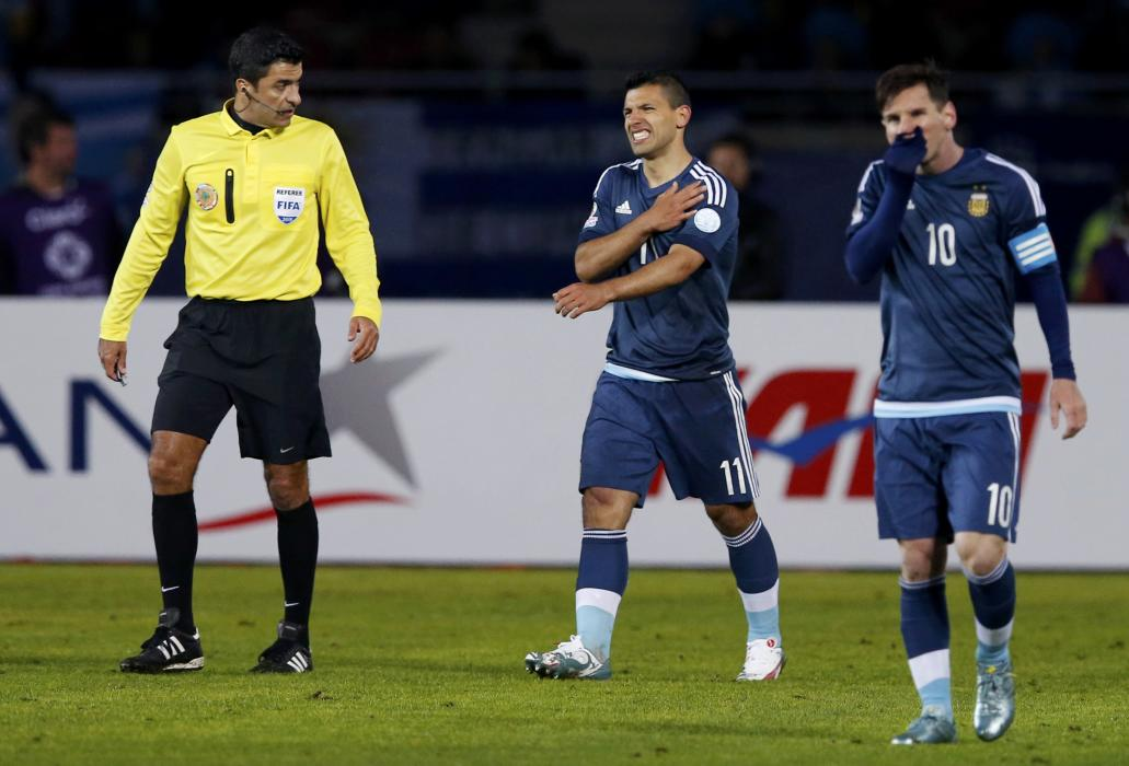 Argentina's Aguero grimaces during the first round Copa America 2015 soccer match against Uruguay as teammate Messi walks nearby at Estadio La...