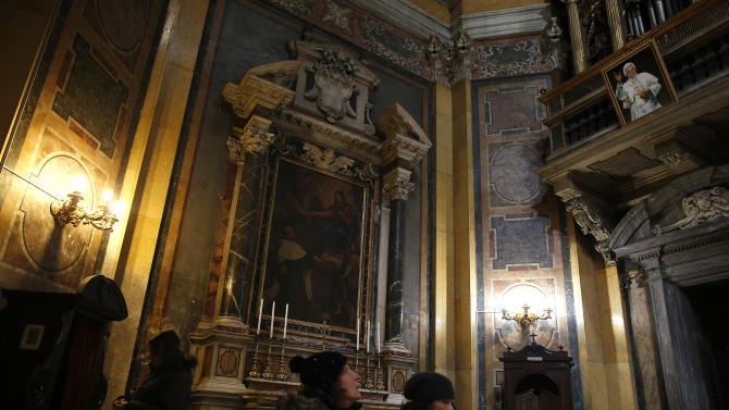 People pray under a portrait of Pope Benedict XVI in a church in downtown Rome