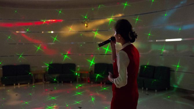 A North Korean woman sings karaoke at the Hyangsan Hotel at the foot of Mount Myohyang, North Korea, Saturday, Feb. 23, 2013. (AP Photo/David Guttenfelder)
