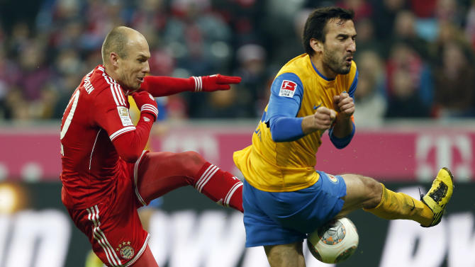 Bayern's Arjen Robben of the Netherlands, left, and Braunschweig's Deniz Dogan of Turkeychallenge for the ball during the German first division Bundesliga soccer match between FC Bayern Munich and Eintracht Braunschweig, in Munich, southern Germany, Saturday, Nov. 30, 2013