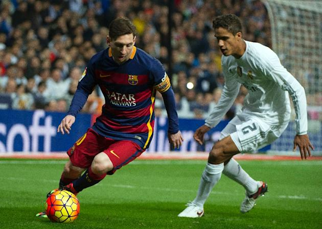 "Barcelona's Lionel Messi (L) slips past Real Madrid's Raphael Varane during their Spanish league ""Clasico"" match at the Santiago Bernabeu stadium in Madrid on November 21, 2015"