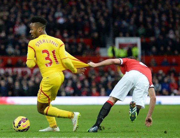 Liverpool's English midfielder Raheem Sterling (L) is held by Manchester United's Spanish midfielder Juan Mata (R) during the English Premier League football match at Old Trafford in Manchester on December 14, 2014
