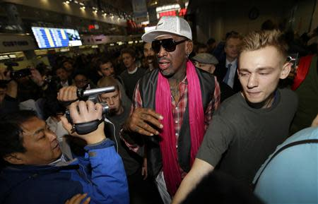Former NBA basketball player Dennis Rodman (C) is surrounded by journalists as he arrives at the Beijing Capital International Airport to leave for Pyongyang, in Beijing, January 6, 2014. REUTERS/Jason Lee