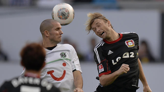 Hannover's Leon Andreasen of Denmark, left, and Leverkusen's Simon Rolfes challenge for the ball during the German soccer Bundesliga match between Bayer Leverkusen and Hanover 96 in Leverkusen, Germany, Saturday, Sept. 28, 2013
