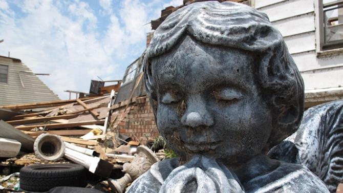 In this Thursday, May 23, 2013 photo, debris cakes the face of this yard angel in front of Shirley Parrish's home in Moore, Okla. The 80-year-old widow escaped to a neighbor's shelter just minutes before Monday's EF5 tornado destroyed her house. (AP Photo/Allen Breed)