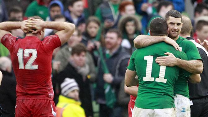 Ireland's Dave Kearney, 11, celebrates with Rob Kearney, as Wales' Jamie Roberts looks dejected after Ireland defeated Wales during their Six Nations Rugby Union international match at the Aviva Stadium, Dublin, Ireland, Saturday, Feb. 8, 2014. (AP Photo/Peter Morrison)