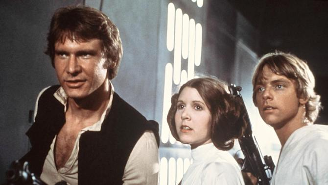 "This publicity film image provided by 20th Century-Fox Film Corporation shows, from left, Harrison Ford as Han Solo, Carrie Fisher as Princess Leia Organa and Mark Hamill as Luke Skywalker in a scene from the ""Star Wars"" movie released by 20th Century-Fox in 1977. The classic Star Wars film that launched a science fiction empire is being dubbed in the Navajo language, with casting calls scheduled Monday, April 29, 2013, in Burbank, Calif., and on May 3 and 4 at the Navajo Nation Museum in Window Rock.  Potential actors don't have to sound exactly like Princess Leia, Luke Skywalker or Han Solo, but should be able to deliver the lines with character. (AP Photo/20th Century-Fox Film Corporation)"