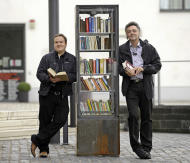 In this picture taken Oct. 10, 2011 Michael Aubermann, right, and Stephan Schilling from the Cologne civic association stand at a public book shelve on a square in Cologne, Germany. Take a book, leave a book. In the birthplace of the printing press, public bookshelves are popping up across the nation on street corners, city squares and suburban supermarkets. In these free-for-all libraries, people can grab whatever they want to read, and leave behind anything they want for others. There's no need to register, no due date, and you can take or give as many as you want. (AP Photo/Martin Meissner)