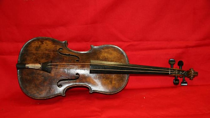 """This is an undated handout image from auction house Henry Aldridge and Son made available on Friday Oct. 18, 2013 shows a violin believed to be the one played by Titanic bandmaster Wallace Hartley will now go on auction. It's a poignant scene familiar to anyone who has watched """"Titanic"""" as the ship slides into the icy waters, musicians perform for the passengers, playing with stoic resolve until the final hour. None of the musicians survived in the 1912 disaster in the North Atlantic. The auction house, which specializes in Titanic memorabilia, expects the violin to fetch more than 200,000 pounds (US$323,300) when it goes on sale Saturday Oct 19, 2013. (AP Photo/Henry Aldridge and Son)"""