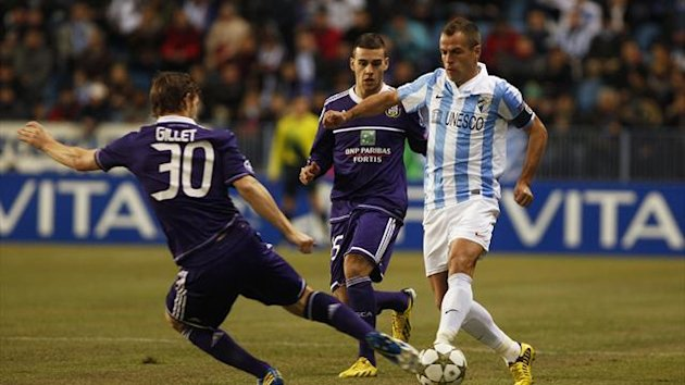 Malaga's Sergio Duda (R) fights for the ball with Anderlecht's Guillaume Gillet (L) during their Champions League Group C soccer match at La Rosaleda stadium in Malaga,