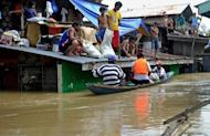 Residents sit marooned on their rooftops after Typhoon Nalgae flooded the town of Calumpit, an agricultural town about two hours north of the capital Manila. The Philippines deployed helicopters, inflatable boats and amphibious vehicles Sunday in a desperate bid to evacuate tens of thousands in the aftermath of successive monster storms