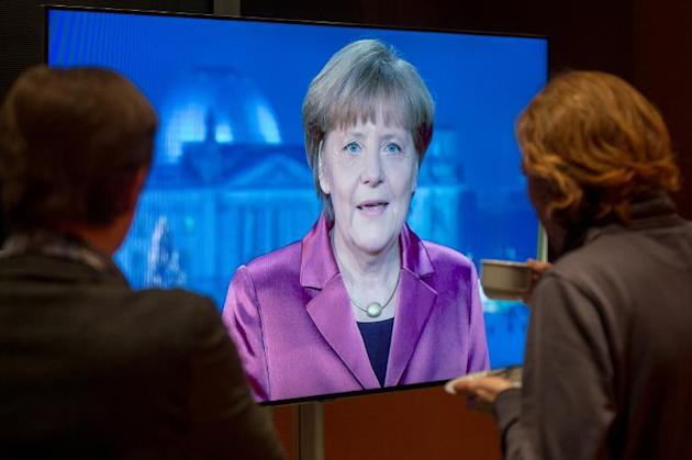 Employees of the chancellery and TV crews watch on a screen as German Chancellor Angela Merkel records her annual New Year's speech at the Chancellery in Berlin on December 30, 2014