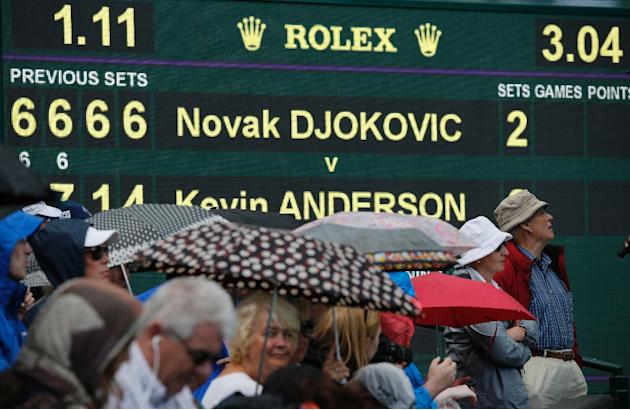 Spectators shelter from the rain as they wait for the conclusion of the delayed men's fourth round match between Serbia's Novak Djokovic and South Africa's Kevin Anderson at the 2015 Wimbl