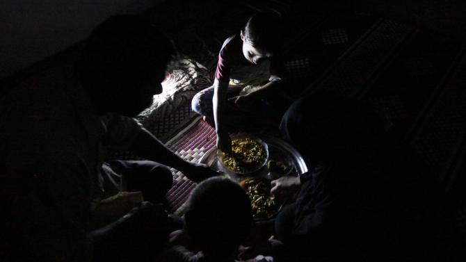 Issa eats dinner with his family inside a weapons factory of the Free Syrian Army in Aleppo