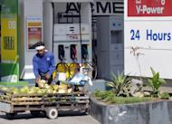 This file photo taken on April 10, 2008 shows a street vendor selling coconuts outside a petrol station in Manila. The Philippines is the world's biggest exporter of coconut products. Supply is not a problem, with 350 million coconut trees growing from the beaches up to the hills and yielding 15 billion fruits a year