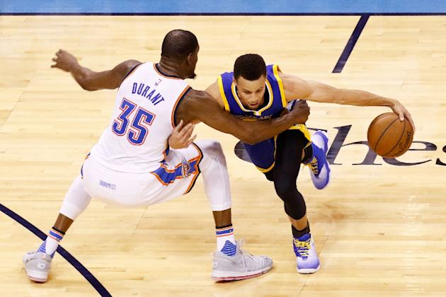 Stephen Curry of the Golden State Warriors drives against Kevin Durant of the Oklahoma City Thunder in game four of the Western Conference Finals