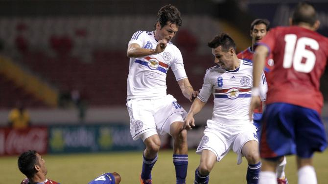 Umana of Costa Rica battles for the ball with Haedo and Perez of Paraguay, as Costa Rica's Gamboa looks on during their international friendly soccer match