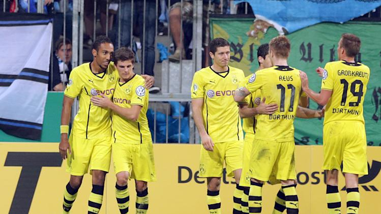 Dortmund's Pierre-Emerick Aubameyang of Gabon, left, celebrates with teammates after scoring his side's opening goal during the German soccer cup second round match between TSV 1860 Munich and Borussia Dortmund, in Munich, southern Germany, Tuesday, Sept. 24, 2013