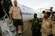 """One of four foreigners captured by Sudanese military in the Heglig oilfield area April 28, is escorted off an airplane in Khartoum. The British embassy was """"urgently"""" investigating on Sunday the arrest in Sudan of one of its citizens, who was among four foreigners the Sudanese military said it captured in the tense Heglig oil region"""