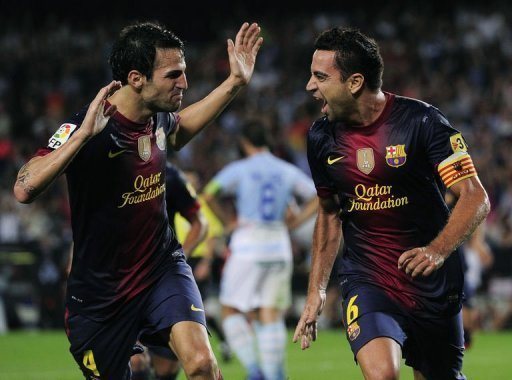 Barcelona's Xavi Hernandez (R) is congratuled by his teamate Cesc Fabregas after scoring during their Spanish La Liga match against Granada at the Camp Nou stadium in Barcelona. Barcelona won 2-0
