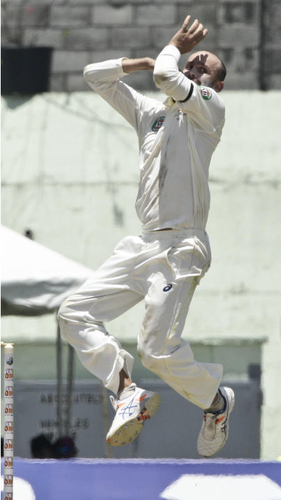 Australia bowler Nathan Lyon bowls during the opening day of their first cricket Test match in Roseau, Wednesday, June 3, 2015. (AP Photo/Arnulfo Franco)