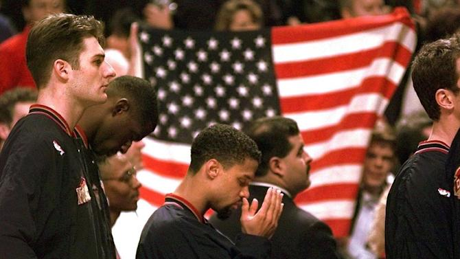 "FILE - In this March 15, 1996 file photo, Denver Nuggets guard Mahmoud Abdul-Rauf stands with his teammates and prays during the national anthem before an NBA basketball game against the Chicago Bulls in Chicago. This was Abdul-Rauf's first game back since he was suspended by the NBA on March 12, 1996, for refusing to participate in the national anthem pre-game ceremony. San Francisco 49ers quarterback Colin Kaepernick's decision this week to refuse to stand during the playing of the national anthem as a way of protesting police killings of unarmed black men has drawn support and scorn far beyond sports. Through the years, ""The Star-Spangled Banner"" has become a symbol of both patriotism and politics. (AP Photo/M. Spencer Green, File)"