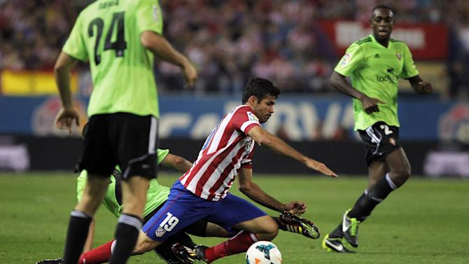 Atletico de Madrid's Diego Costa from Brazil, centre controls the ball in between Osasuna's palyers during a Spanish La Liga soccer match at the Vicente Calderon stadium in Madrid, Spain, Tuesday, Sept. 24, 2013