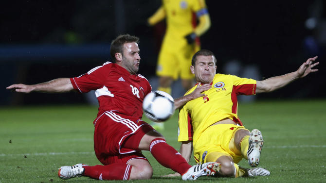 Romania's Matel fights for the ball with Andorra's Manel Ayala during their 2014 World Cup qualifying soccer match at Estadi Comunal in Andorra