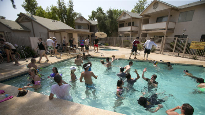 People play in a pool in an apartment complex in Tempe, Ariz. during the Tempe Bicycle Action Group swimsuit ride on Saturday, June 29, 2013. About 100 cyclists biked around the city cooling off in pools and fountains. (AP Photo/The Arizona Republic, David Wallace)