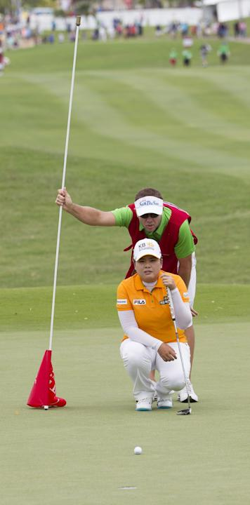 Inbee Park, bottom, of South Korea, reads the first green with the help of her caddie in the third round of the LPGA LOTTE Championship golf tournament at Ko Olina Golf Club, Friday, April 18, 2014, i