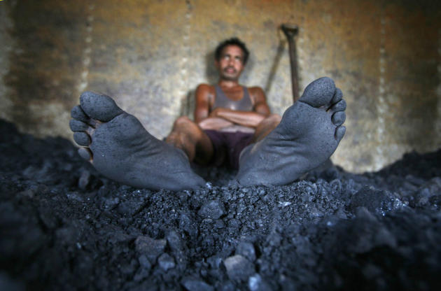 A labourer rests inside the wagon of a coal train